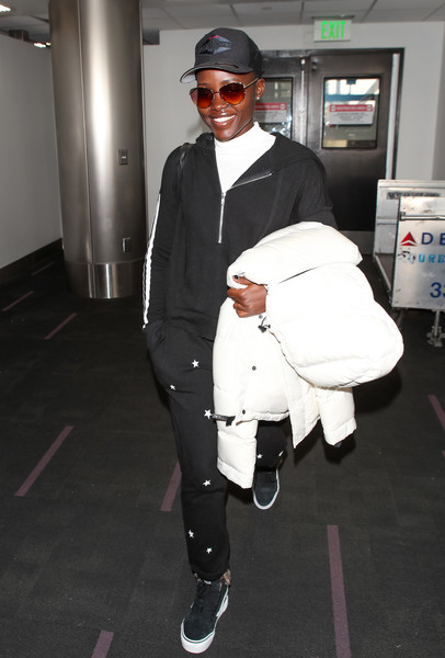 Lupita Nyong'o stayed comfy in a black hoodie while catching a flight.