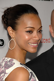 At the 'Machine Gun Preacher' premiere Zoe Saldana wore her hair swept back and collected in twists at the back of her head. To try her look, smooth back hair into a ponytail, twist one-inch sections and pin into place.