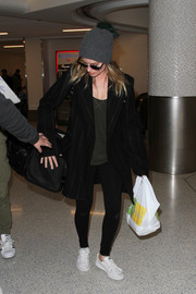 Margot Robbie made her way through the airport carrying a black dog carrier duffle by Sleepypod.