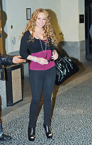 Mariah is wearing open toed ankle boots in black leather.