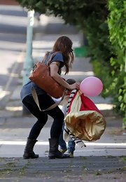 Mel C carried a camel-colored cross-body tote as she left a birthday party with her daughter.