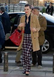 Milla wore a pair of cute plaid pants while out in Madrid. She paired her funky pants with a red leather tote bag.