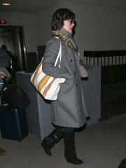 Milla Jovovich flew out of LAX wearing black wedge boots and a glen plaid coat.