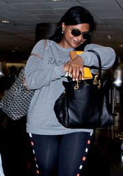 Mindy Kaling accessorized with a black leather tote for a flight.