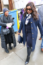 Mindy Kaling matched her outfit with a navy leather purse.