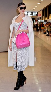 Miranda Kerr landed in Japan carrying a hot-pink bucket bag that injected a welcome pop of color to her monochrome outfit.