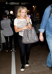 Miranda Lambert kept her look casual with a graphic tee paired with black and white lace-up canvas shoes.