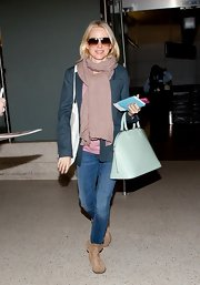 Naomi Watts traveled in style with a classic solid scarf.