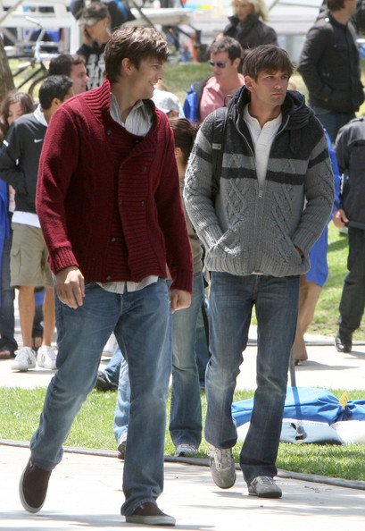 Ashton looked laid back-cool in a cardigan, jeans and canvas slip-on sneakers.