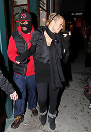 Mariah Carey bundled up for winter in a black glittering scarf and fuzzy boots.