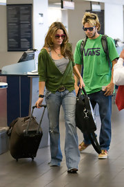 Nikki carries a brown rollerboard through LAX.