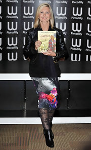Olivia Newton-John promoted her cookbook wearing a black top, a print skirt and a leather jacket.