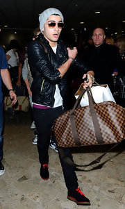 Zayn Malik travels in style.  He's wearing a black leather biker jacket and skinny jeans.