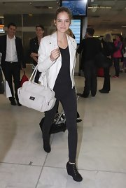 Barbara Palvin races through the airport in a white jacket over all black jeans and top.