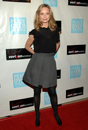 Calista Flockhart donned timeless black plumps over opaque black tights. She paired the simply chic footwear with a gray full skirt.