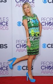Paris Hilton accented her patterned dress with a pair of blue suede platform pumps.