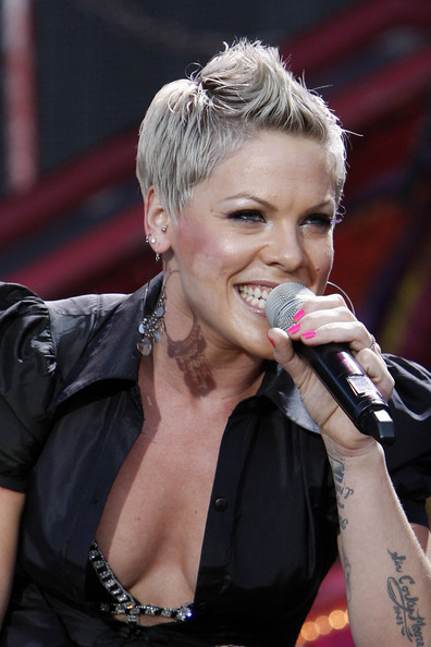 Pink has several body piercings, including this tragus piercing. The tragus projects immediately in front of the ear canal.