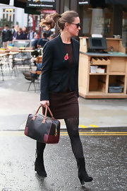 Pippa Middleton accessorized her stylish aubergine sheath with a black leather tote with tan handles and burgundy accents.