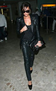 Victoria Beckham caps off her all-black airport ensemble with a fierce black clutch.