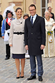 Princess Victoria looks chic in a winter white coat by H&M. The coat features a fold over neckline and a black flowered belt.