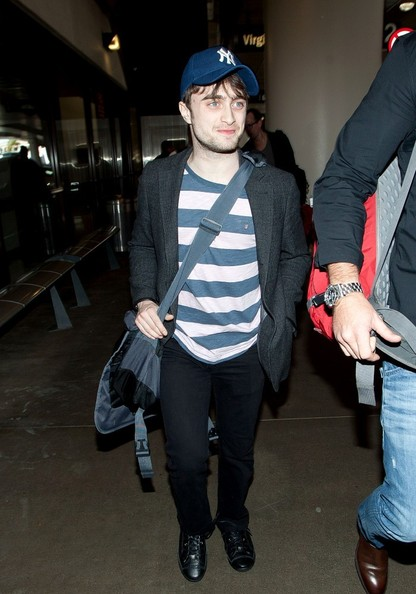 Daniel Radcliffe dressed up a striped knit top with a gray blazer while arriving on a flight in LA.