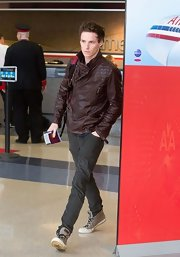 Eddie Redmayne traveled in style when he donned this brown classic motorcycle jacket.