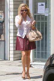 Reese Witherspoon completed her casual-chic look with a pleated purple mini skirt, also by Draper James.
