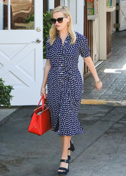 For her arm candy, Reese Witherspoon chose a chic red leather tote by Coach X Selena Gomez.