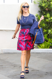 Reese Witherspoon dressed up her tee with a vibrant floral skirt by Draper James.