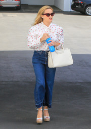 Reese Witherspoon teamed her blouse with a pair of wide-leg jeans by Veronica Beard.