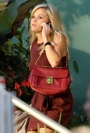 While filming scenes for her next movie, Reese showed off a vibrant red shoulder bag.