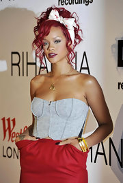 Rihanna wears a darling pin-up girl polka-dot headband with this funky outfit.