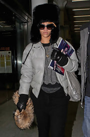 Always one to sport extravagant accessories, Rihanna makes her way through the airport wearing a faux fur fox trapper hat in black. The girl can do no wrong even in this massive fur hat.