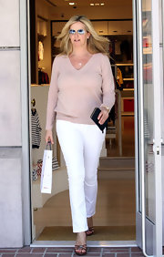 Penny Lancaster teamed up her V-neck sweater with a pair of white pants while shopping around Beverly Hills.