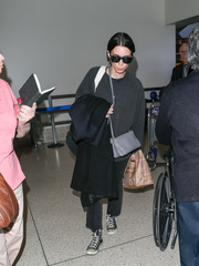 Rooney Mara accessorized with a gray leather shoulder bag for a flight.