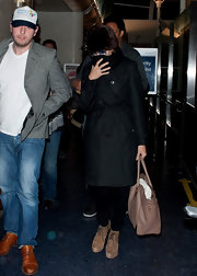 Eva Mendes shielded her face behind a scarf when arriving at LAX with boyfriend Ryan Gosling while wearing a knee-length trench coat.