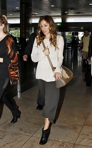 SJP traveled in style in an off-white comfy sweater paired with black leather ankle boots.