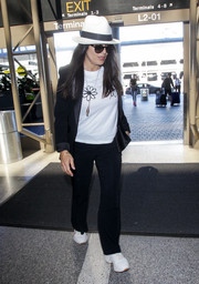 Salma Hayek departed on a flight at LAX wearing a black suit with satin lapels.
