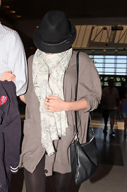 Scarlett hid from the photog's as she showed off her casual style while leaving LAX airport. She carried a simple leather shoulder bag,which was a great addition to her scarf and hat.