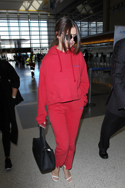 Selena Gomez caught a flight at LAX looking sporty in a red Vetements hoodie.