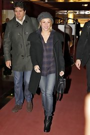 Shakira kept her famous body under wraps at the airport in a black shawl collar coat and jeans.