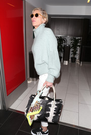 Sharon Stone caught a flight out of LAX carrying a chic monochrome snakeskin tote.
