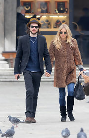 Sienna Miller kept warm while out and about town in skinny jeans tucked into black suede knee-high boots.