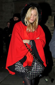 Sienna Miller carried a unique quilted shoulder bag. She paired the gold chained bag with a fur trimmed red cape.