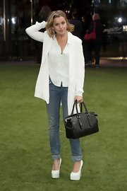Caggie Dunlop went basic with the color scheme of her outfit by opting for a pair of white pumps to match her top and cardigan.