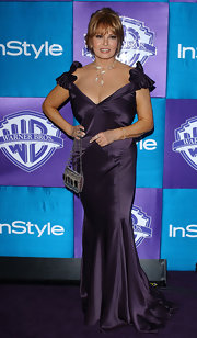 Raquel Welch styled her look with a silver beaded purse.