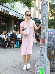 Suki Waterhouse paired her dress with white peep-toe wedges.
