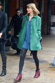 Taylor Swift sported a cool mix of colors with this green Katherine Hooker coat and  blue mini dress combo while out in New York City.