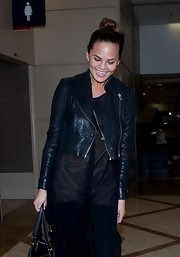 Chrissy Teigen chose a cropped leather jacket for her travel look while arriving at LAX.