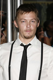 Norman wears a classic skinny black tie with his white shirt and suspenders.